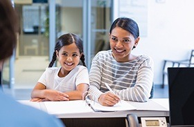 Smiling mother and daughter at reception desk
