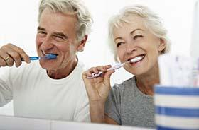 Woman in dental chair smiling at dentist