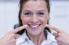 Woman pointing to repaired smile