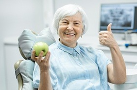 Older woman in dental chair giving thumbs