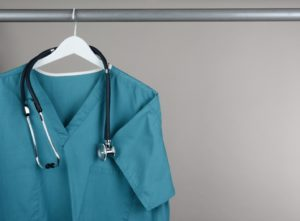 freshly cleaned scrubs and stethoscope hanging in dental office closet
