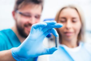 dentist using model to explain dental implants in Hamden